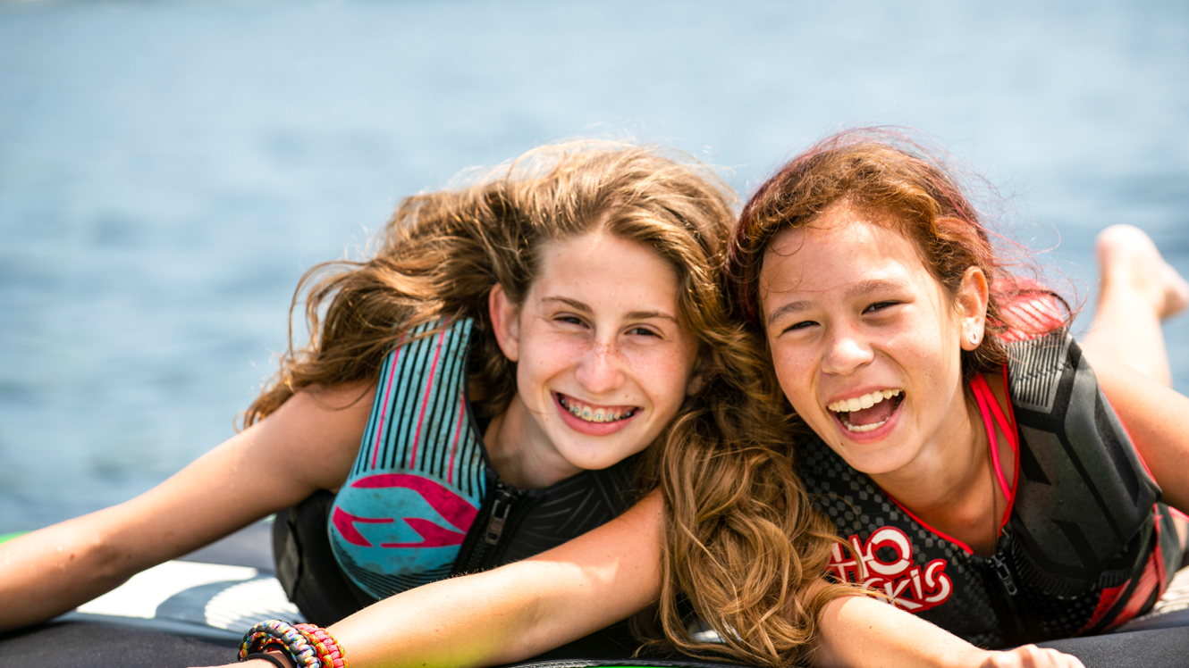 Smiling girls on inflatable tube at summer camp