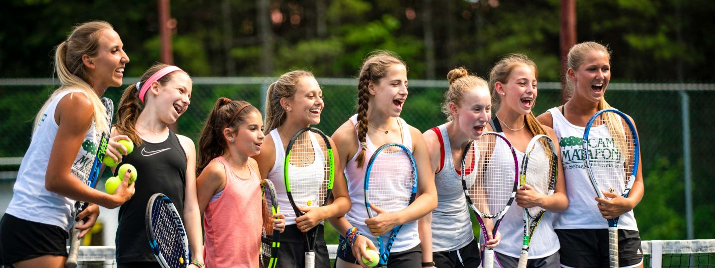 girls standing together on a tennis court