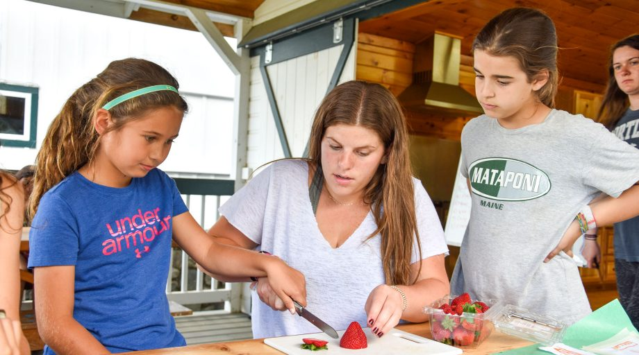 a camp counselor showing girls how to properly cut a strawberry