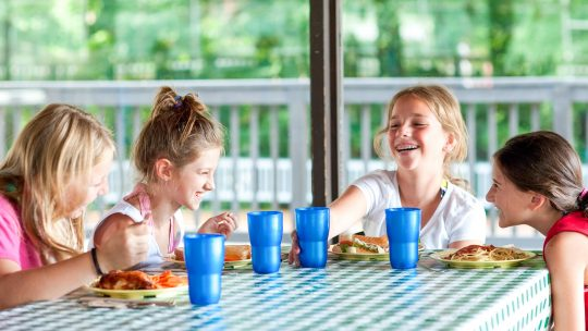 Laughing campers sit around lunch table