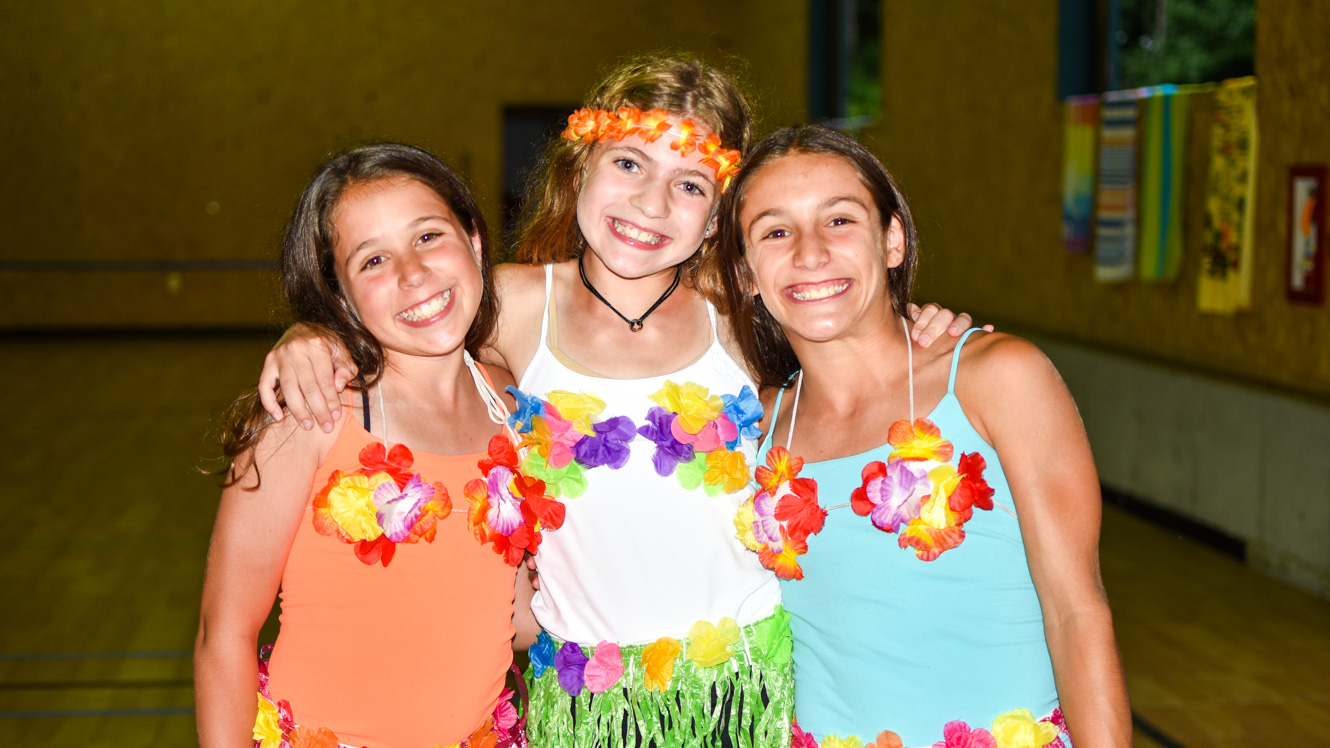 Three campers wearing leis and grass skirts