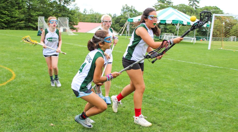 Girls play lacrosse game at summer camp