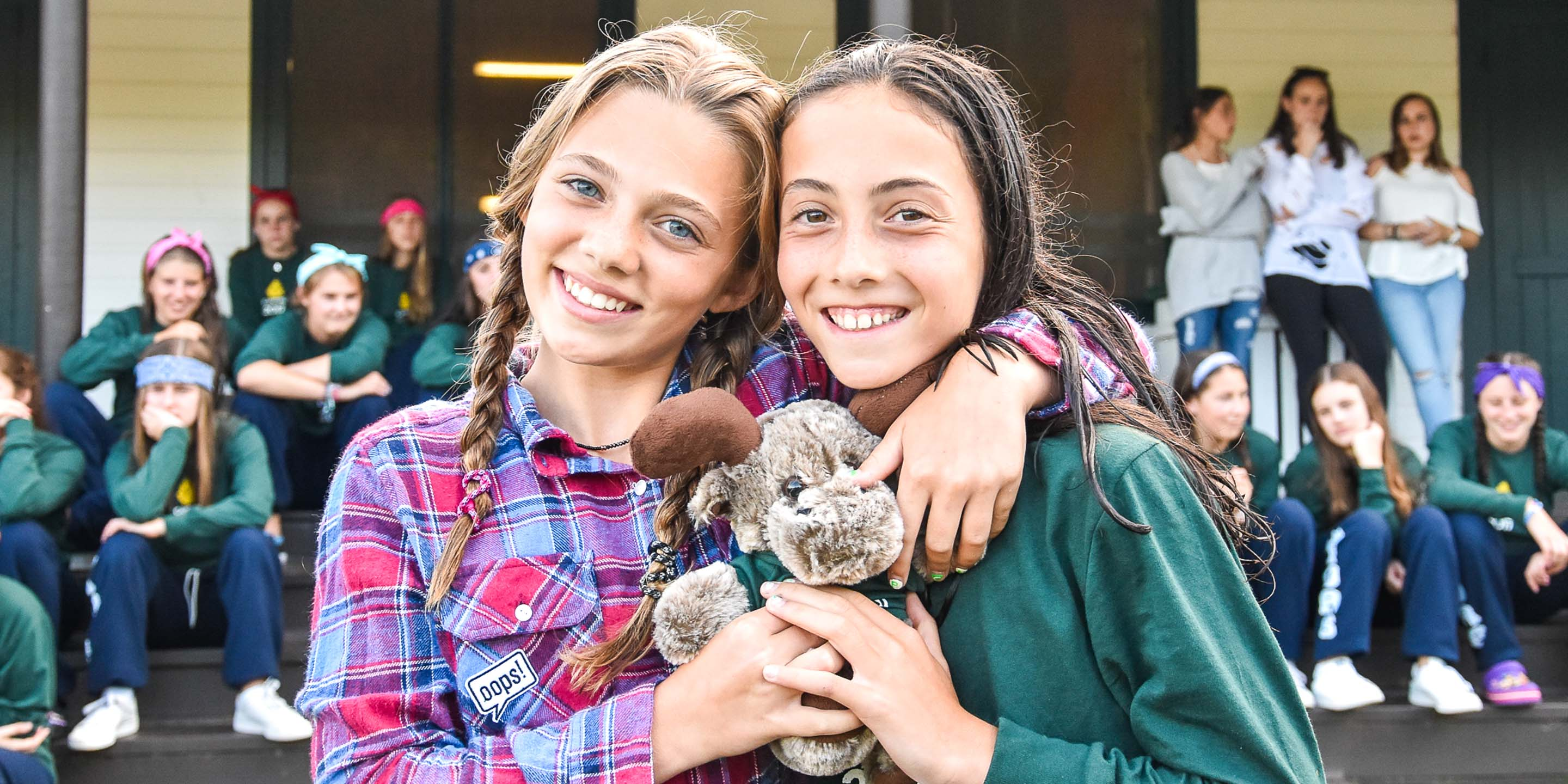 Two girls smile at camera while holding moose plush