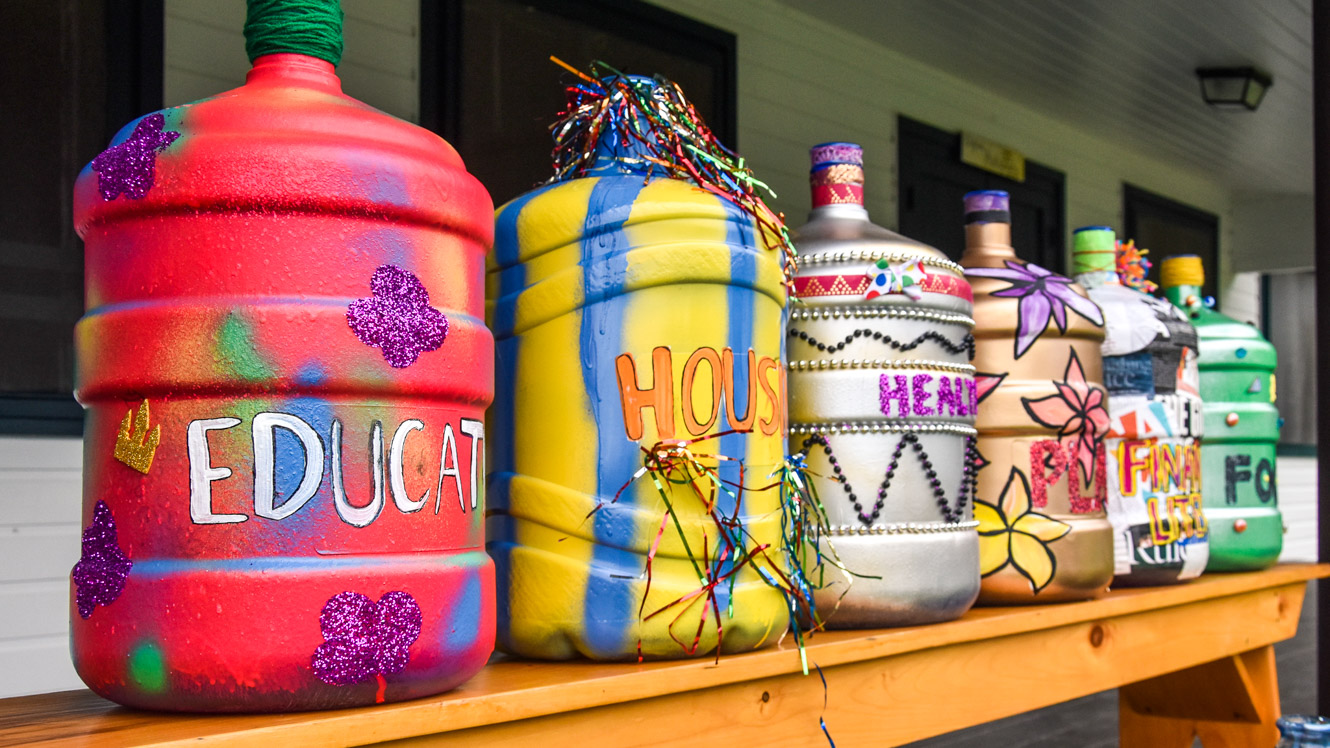 Colorfully painted jugs sit in a row on a shelf