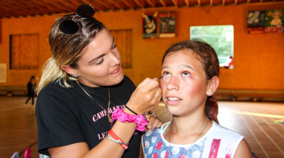 a camp counselor applying performance make up to a camper's face