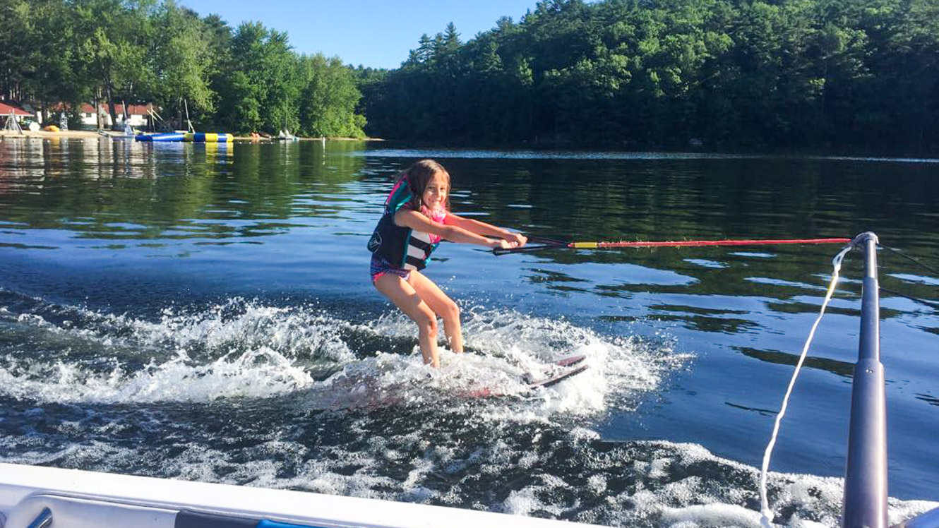 Smiling camper holds rope to waterski