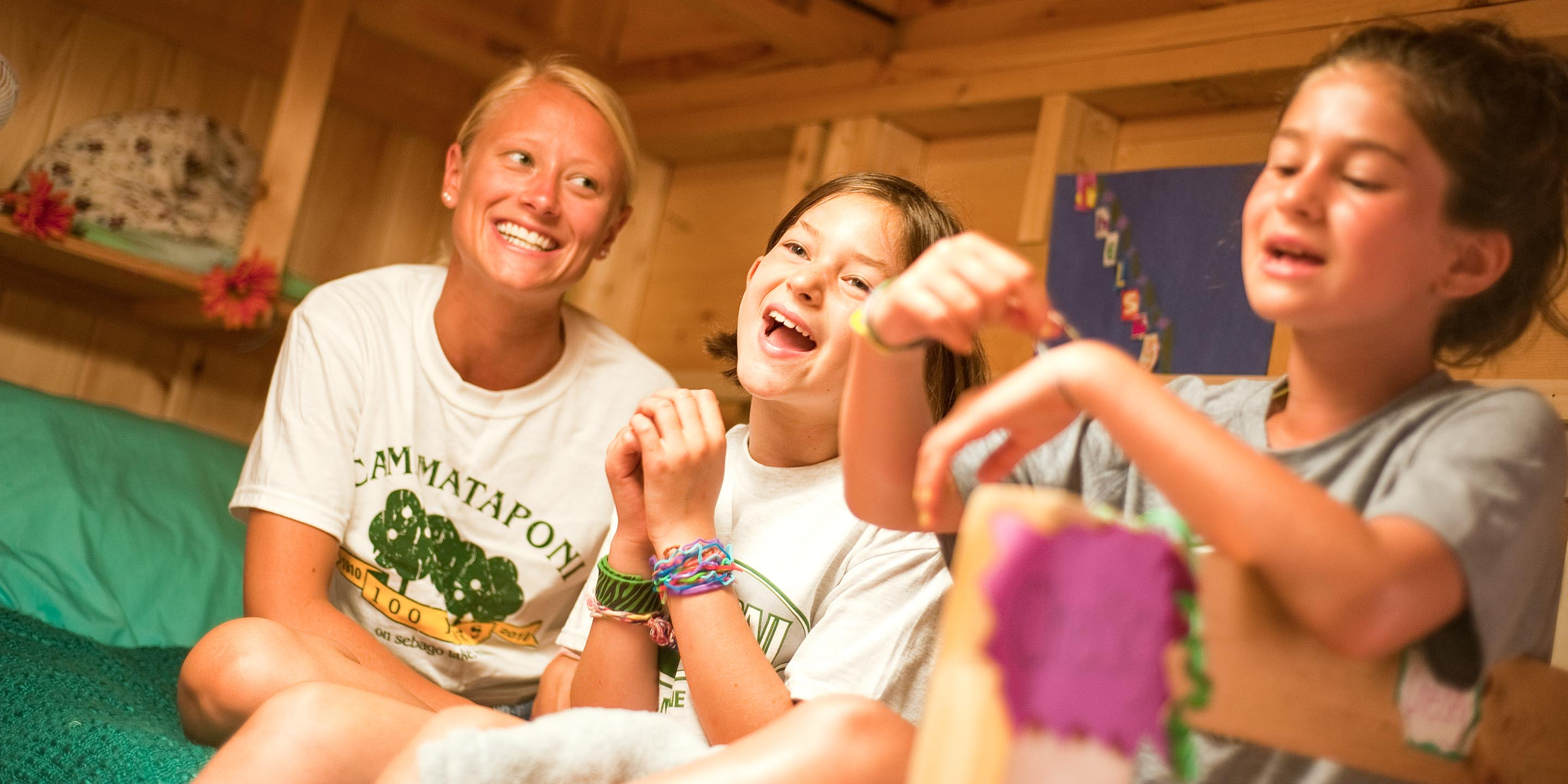Counselor and campers laugh on camp bunk