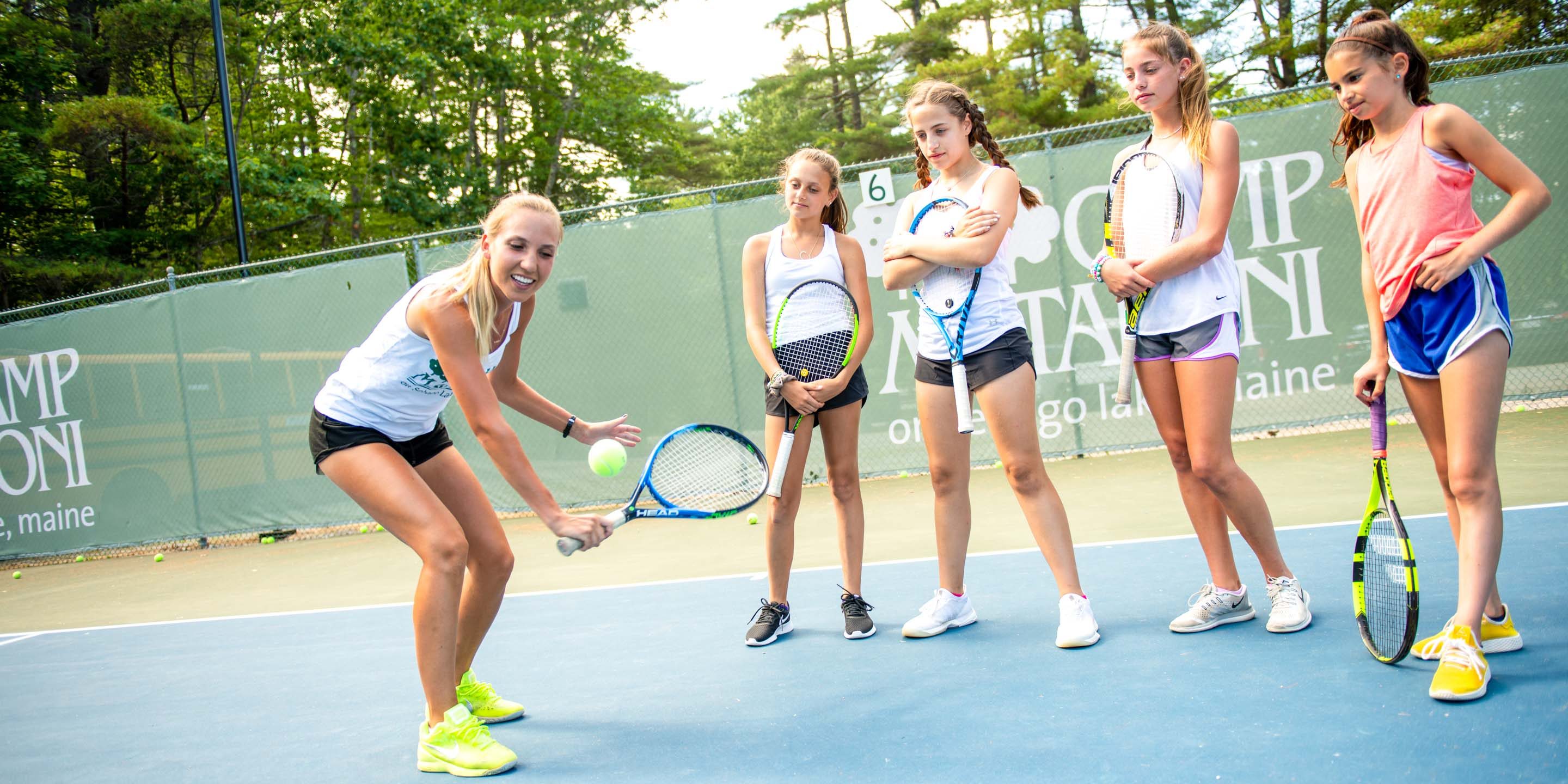 Counselor teaches campers how to play tennis