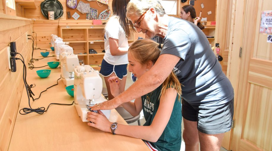 Older woman helps camper with sewing machine
